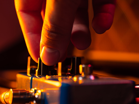 Musician tuning guitar effect pedal for best music during concert on stage. Guitarist tapping on it for different sounds. Macro view. Banco de Imagens