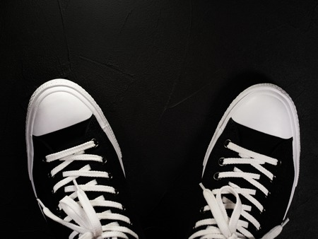 Black sneakers with white shoelaces. Classic vintage trendy shoes on black monocrome background. Copy space Banco de Imagens - 110543530