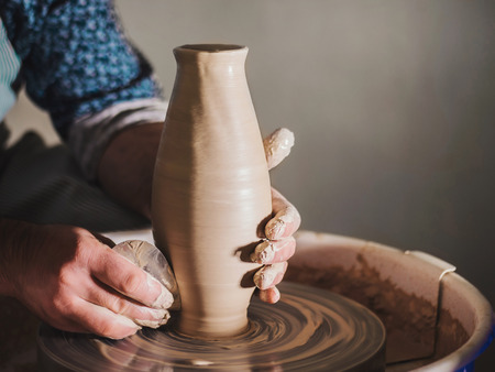 Creating earthenware and traditional pottery concept. Experienced male potters hands creating beautiful clay product - vase - using professional tools. Banco de Imagens
