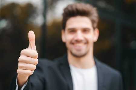 Winner. Success. Brunette young man in business clothing in office district smiles to camera and gives thumbs up. Happy guy showing gesture of approval.