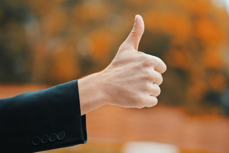 Winner. Success. Hand of man in business clothing gives thumbs up. Guy showing gesture of approval Banco de Imagens