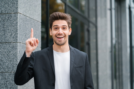 Smiling happy student man showing eureka gesture. Portrait of young thinking pondering businessman having idea moment pointing finger up on office building background