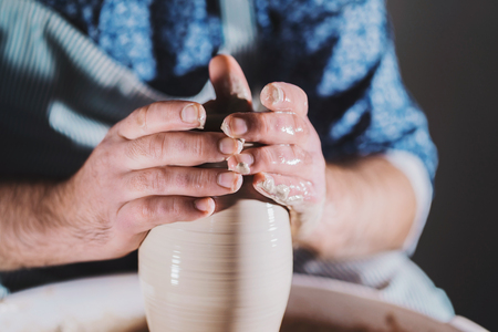 Artist operates hands, which gently creating correctly shaped handmade from clay. Traditional pottery making, teacher shows the basics of pottery in art studio Banco de Imagens - 110543860