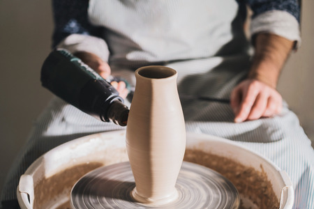 Experienced male potter blows dry the clay, he creating beautiful clay product - jug - using professional tools. Toned cinematic, craft factory authentic. Banco de Imagens - 110543861