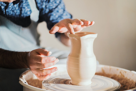 Potter creates jug nose, works on details and functionality of the product. Male artist operates hands, which gently creating correctly shaped handmade from clay.