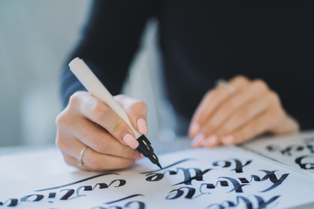 Calligrapher hands writes phrase on white paper. Inscribing ornamental decorated letters. Calligraphy, graphic design, lettering, handwriting, creation concept