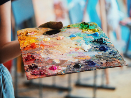 Wooden art palette with oil paints. Mixing colors together. Artistic instrument with many colors. Working tool with squeezed out tubes of paint. Banco de Imagens - 111486578