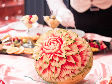 Close up of carved watermelon as rose in the restaurant. Carving on fruits and berries. Banco de Imagens