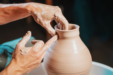 Unknown craftsman creates jug. Focus on hands only. Small business, talent, inspiration concept. Overhead view. Working process of mans work at potters wheel in art studio Banco de Imagens