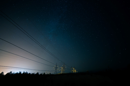 Incredible night sky with stars, Milky Way passing over power line in long exposure timelapse. Beautiful panorama view. Nature in the countryside. Astro photography Banco de Imagens
