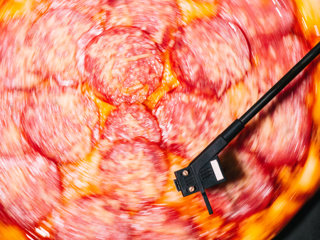 Party with delicious junk food. Italian pizza with salami sausage and cheese spinning on turntable vinyl player as vinyl record Banco de Imagens