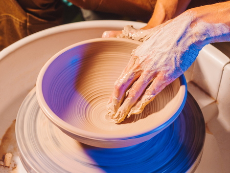 Creating earthenware and traditional pottery concept. Experienced male potters hands creating beautiful clay product - bowl - using professional tools. Toned cinematic, craft factory authentic Banco de Imagens