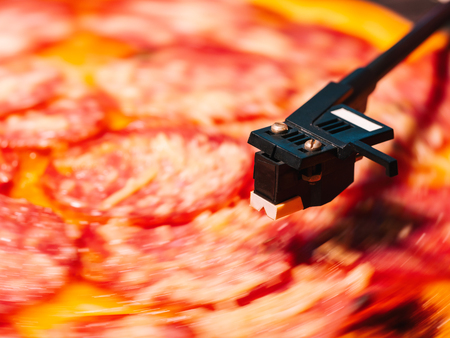 Pizza pepperoni spinning on turntable vinyl player. Concept of party, delicious junk food. Italian pizza with salami sausage and cheese. Banco de Imagens