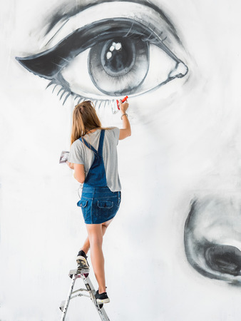 Graffiti Artist Drawing face of beautiful woman with paint on Street Wall. Female working with brush. Urban Outdoors Art Concept Banco de Imagens - 112150719