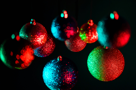 New 2019 year mood. Christmas tree toys, shining balls on black wall. Decoration. Abstract blurred bokeh holiday background.