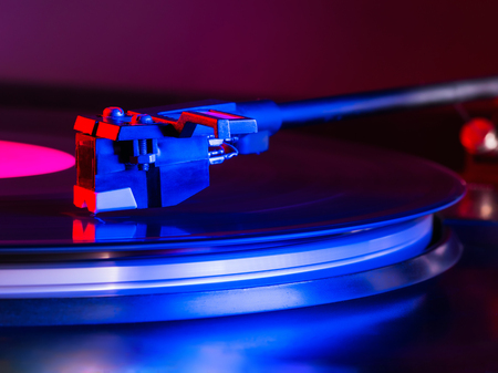 Cinemagraph, retro record vinyl player. Record on turntable. Top view close up. Loop-able Vintage photo of Old Gramophone, playing a music. Neon light. Banco de Imagens - 113058848