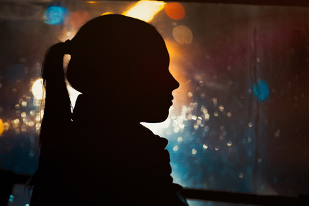 Silhouette of young girl on night city bokeh background. Rain drops running down the window. Autumn season