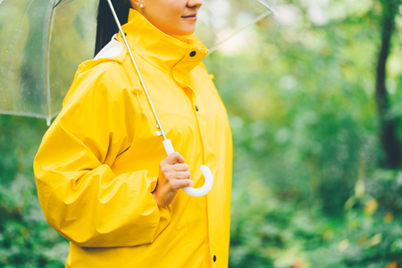 Attractive unrecognizable young girl in yellow raincoat in park or forest with transparent umbrella, autumn day. Focus on hands