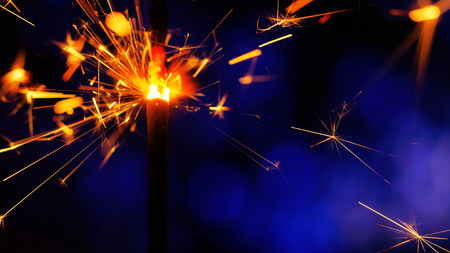 Sparkler Over Blue. Gun powder sparks shot against deep dark background. Burning fuse or bengal fire Isolated. Mojo-style coloring. Lightening Christmas sparkler. Stock Photo