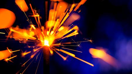 Sparkler Over Violet. Gun powder sparks shot against deep dark background. Burning fuse or bengal fire Isolated. Mojo-style coloring. Lightening Christmas sparkler Banco de Imagens - 113058865