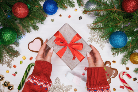 Hands in warm sweater holding gift in silver paper with red bow. Wooden white table with Christmas decorations - spruce branches with christmas balls, gingerbread, lollipops. Banco de Imagens - 113085725