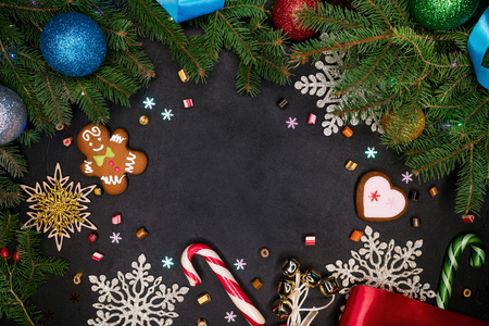 Copy space Christmas background - black surface with new year holidays decorations - spruce branches with colorful balls, gingerbread, lollipops, snowflakes. Top view
