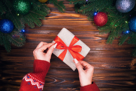 Female hands in warm red sweater corrects red bow on present in silver paper. Wooden vintage table with Christmas decorations. Top plan view. Festive mood, new year concept. Banco de Imagens - 113085729