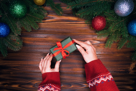 Female hands puts gift wrapped in emerald paper with red ribbon on retro wooden table with Christmas decorations - green spruce branches, christmas balls. Top plan view.