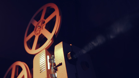 Vintage objects, cinematograph concept. Retro film projector playing in the dark room. Old-fashioned antique super 8mm film projector projecting beam of light