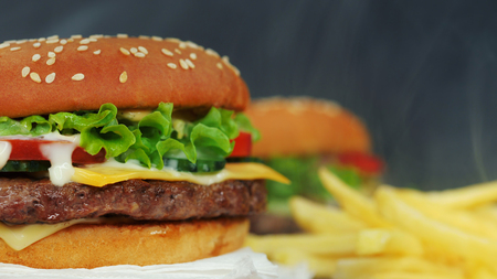 Big appetizing burger with meat cutlet, vegetables, cheese, lettuce and sauce. Hamburger rotates on other meal background, close-up view. Unhealthy yummy food concept