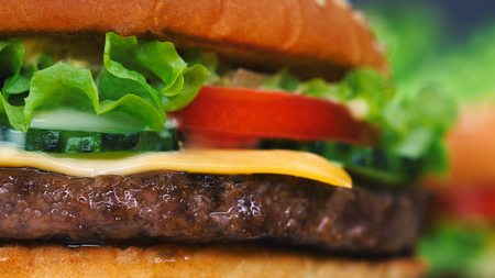 Macro detailed view of juicy beef burger layers. Cutlet, onion, vegetables, melted cheese, lettuce, sauce and topped sesame seeds. Hamburger. Junk fast food concept