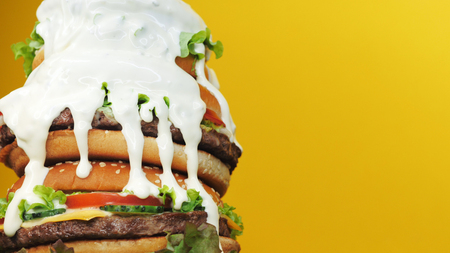 Huge fresh burger as cake. Mayonnaise fat sauce poured from top. Yellow background. Fastfood, unhealthy food concept. Copy space