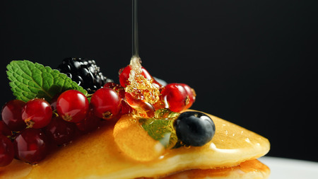 Stack of fresh fluffy pancakes decorated on top with forest berries on plate and pouring honey syrup. Delicious, healthy american breakfast. Fresh bakery concept