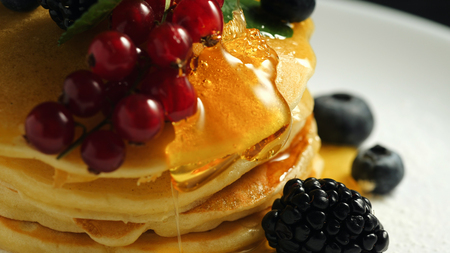 Stack of homemade pancakes or crepes decorated on top with forest berries - red currant, blackberry and blueberry. Delicious, healthy classic american breakfast. Close-up.