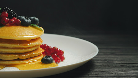 Fresh bakery. Pancakes with forest berries and honey on white plate and black smoke background. Copy space. Homemade healthy breakfast. Yummy food, dessert concept. Banco de Imagens - 114171149