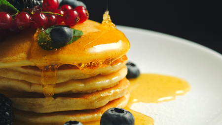 Stack of homemade pancakes or crepes decorated on top with forest berries - red currant, blackberry and blueberry. Delicious, healthy classic american breakfast. Close-up. Banco de Imagens - 114171150