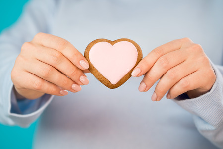 Pregnant woman holding heart-shaped cookie on tummy belly background. Young girl in blue wearing expecting baby. Maternity, motherhood, pregnancy, love concept.