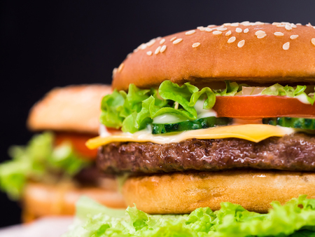 Fresh yummy grilled burgers on black background. Meat patty, tomatoes, cucumber, lettuce and sesame seeds. Fast food concept. junk food lifestyle Banco de Imagens