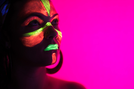 Fashion sexy dancer in neon light. Fluorescent makeup glowing under ultraviolet light. Night club, party, halloween psychedelic concepts. Mysterious woman with UV painting