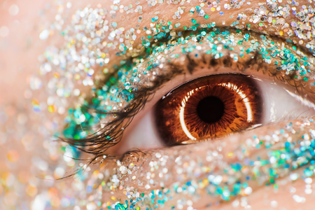 Macro brown female eye with glitter eyeshadow, colorful sparks, crystals. Beauty background, fashion glamour makeup concept. Holiday evening make-up detail.