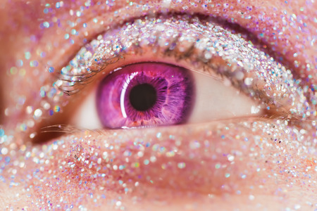 Macro violet or pink female eye with glitter eyeshadow, colorful sparks, crystals. Beauty background, fashion glamour makeup concept. Fantasy look. Holiday evening make-up detail.
