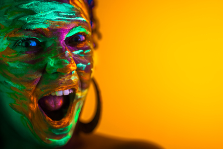 Portrait of girl with fluorescent paint makeup. Dye glowing near UV light. Woman with open mouth in neon light. Night club, party, halloween psychedelic concepts Banco de Imagens - 114516284
