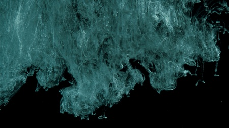Ink in water. Turquoise with silver glitter paint reacting in water creating abstract cloud formations Banco de Imagens
