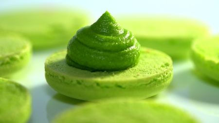 Green pistachio macarons, squeezing and adding cream filling from pastry bag. Macaroons - delicious and beautiful french dessert. Cooking, food and baking, pastry concept