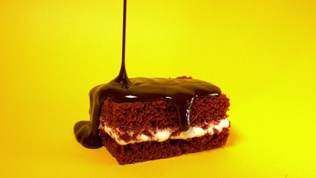 Chocolate topping glaze pouring on biscuit cake dessert on yellow background. Sweet decoration. Cooking, food and baking, pastry shop concept Banco de Imagens