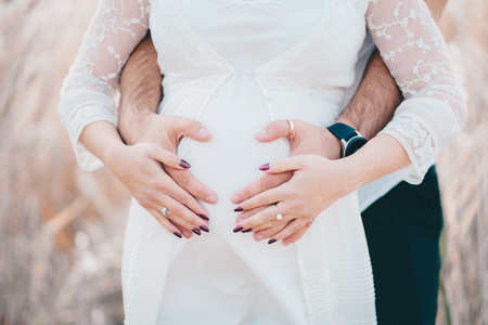 Hands of future parents - unrecognizable man and woman on pregnant belly background
