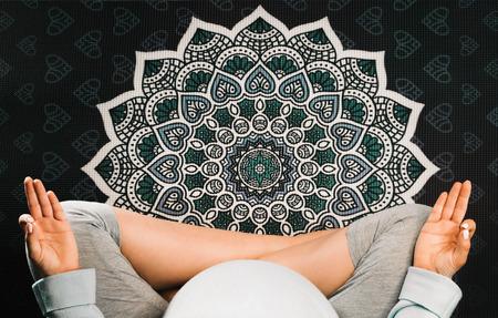 Pregnant woman sitting in lotus position on mandala yoga mat and meditating. Top view