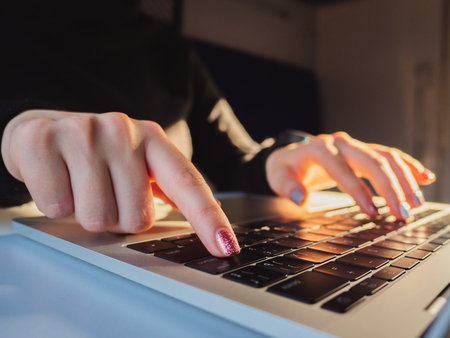 Young business woman working on laptop. Focus on hands typing on keyboard. Sunrise or sunset light leaks