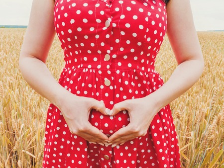 Pregnant unrecognizable woman in polka dot red dress standing in wheat field and showing heart symbol on her belly background. 版權商用圖片