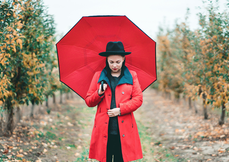 Woman in red coat and with umbrella between trees in apple garden at autumn season. Beautiful portrait of caucasian girl Imagens